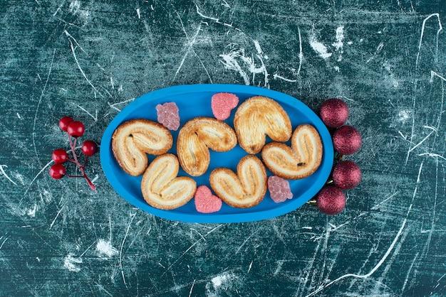 Smaczne ciasteczka z cukierkami galaretki cukrowej na niebieskim pokładzie. zdjęcie wysokiej jakości