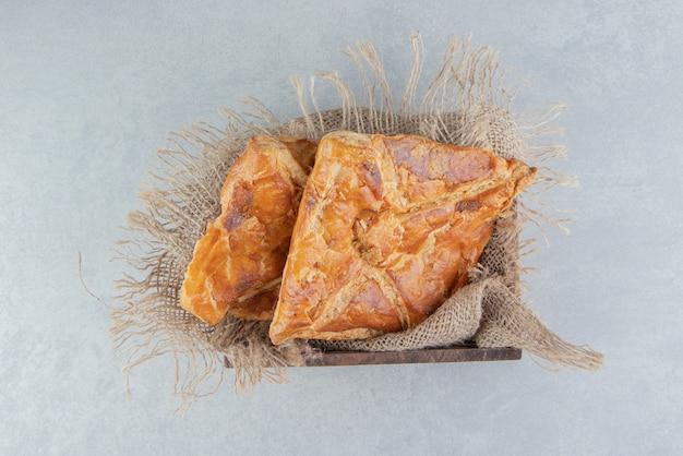 Smaczne ciastka chaczapuri w drewnianym pudełku.
