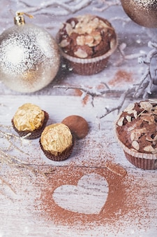 Smaczne ciastko czekoladowe ze słodyczami, kakao w kształcie serca i zimową dekoracją na białym rustykalnym drewnianym stole. zimowe wakacje tło.