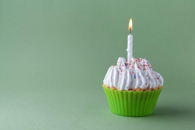Smaczne ciastko urodzinowe ze świecą, na zielonym tle