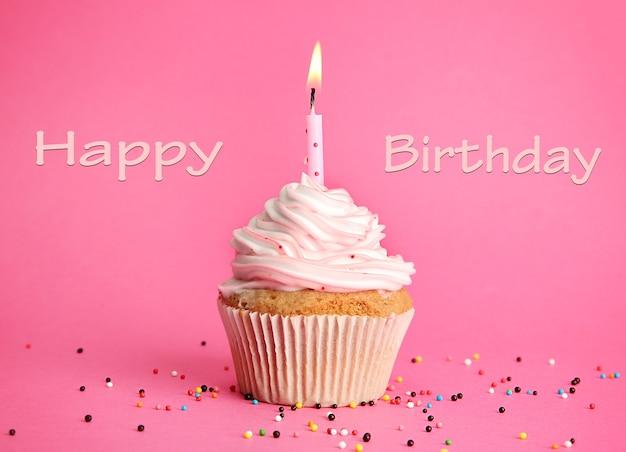 Smaczne ciastko urodzinowe ze świeczką, na różowym tle