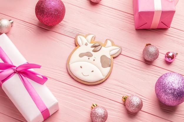 Smaczne ciastko w kształcie byka, prezentów i świątecznego dekoru różowy drewniany stół