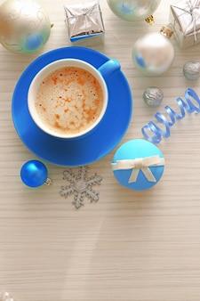 Smaczne ciastko z kokardą, filiżanką kawy i świątecznymi zabawkami na kolorowym drewnianym tle
