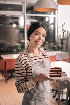 Smaczne ciasto. atrakcyjna przedsiębiorczyni w pasiastym fartuchu trzymająca smaczny tort ze swojej kawiarni