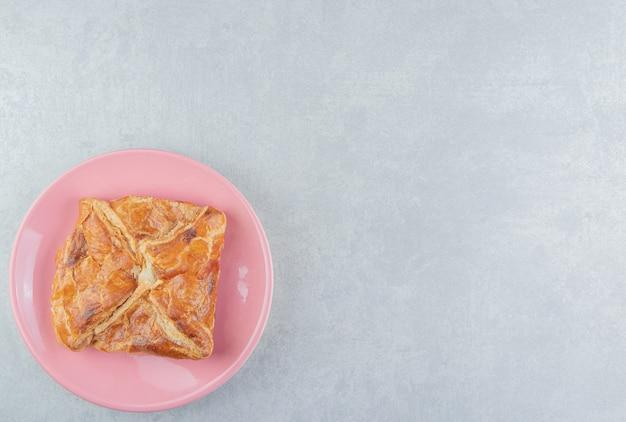 Smaczne ciasto chaczapuri na różowym talerzu.