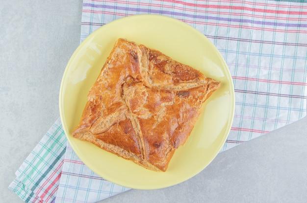 Smaczne ciasto chaczapuri na żółtym talerzu.
