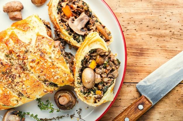 Smaczne ciasto grzybowe lub grzyb wellington na starym drewnianym stole. angielskie jedzenie