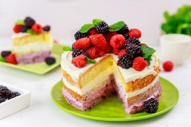 Smaczne ciasto jagodowe ozdobione świeżymi malinami i jeżynami na białym tle.