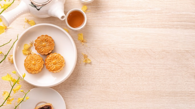 Smaczne ciasto księżycowe na festiwal w połowie jesieni na jasnym drewnianym stole, koncepcja świątecznej popołudniowej herbaty ozdobionej żółtymi kwiatami, widok z góry, płasko świecki