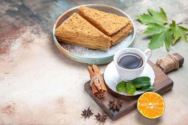 Smaczne ciasto miodowe z filiżanką herbaty na świetle