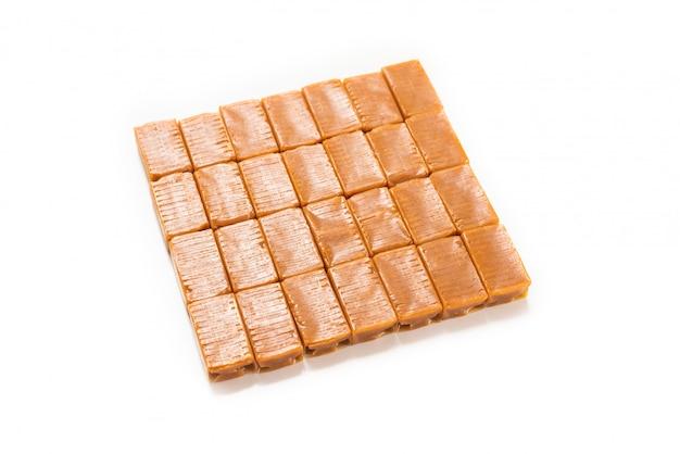 Smaczne cukierki karmelowe na białym tle