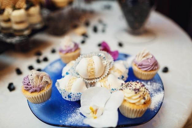 Smaczne cupcakes ze śmietany serwowane na niebieskim naczyniu