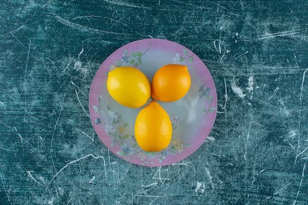 Smaczne cytryny na talerzu, na marmurowym stole.