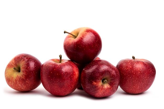 Smaczne czerwone jabłka na białym tle na białym stole.