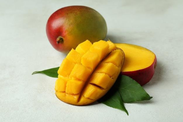 Smaczne dojrzałe owoce mango na białej teksturowanej powierzchni