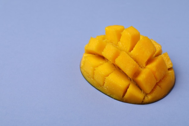 Smaczne dojrzałe owoce mango na fioletowej powierzchni