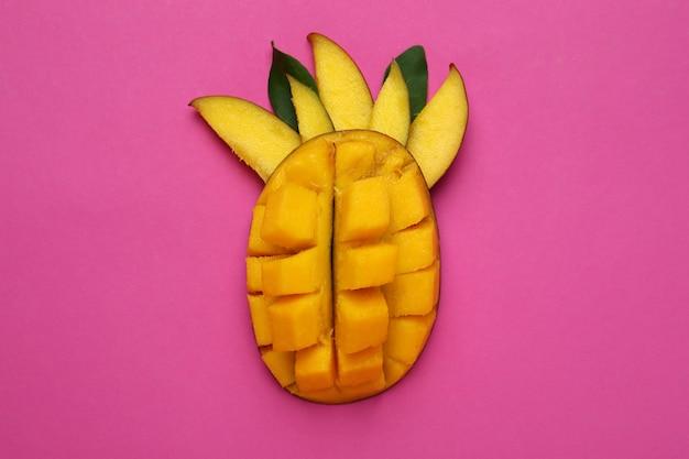 Smaczne dojrzałe owoce mango na różowej powierzchni