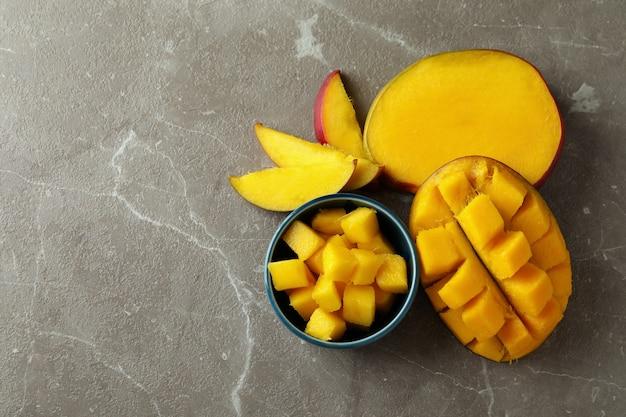 Smaczne dojrzałe owoce mango na szarej teksturowanej powierzchni