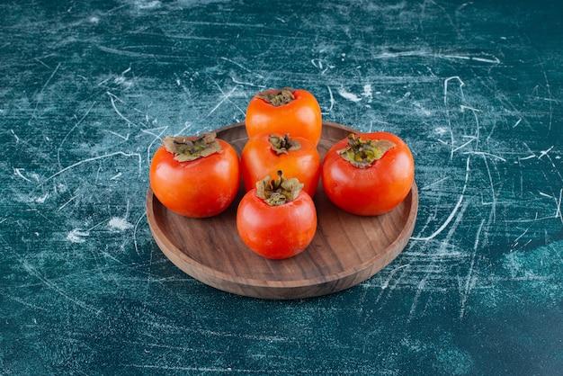 Smaczne dojrzałe persimmons na drewnianym talerzu.