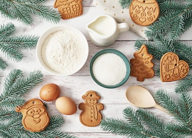 Smaczne domowe ciasteczka imbirowe. składniki do gotowania wypieków, naczynia kuchenne, piernik. kartkę z życzeniami szczęśliwego nowego roku. stół świąteczny. jodła, sosna.