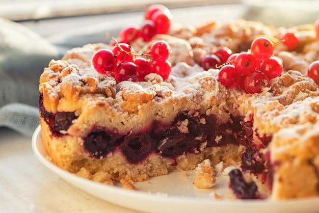 Smaczne domowe ciasto wiśniowe i świeże czerwone porzeczki.