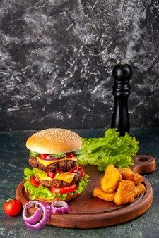 Smaczne domowe pomidory kanapki papryka na deska do krojenia cebula pomidor z łodygą bryłki kurczaka na ciemnym kolorze powierzchni