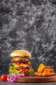 Smaczne domowe pomidory kanapki papryka na drewnianej desce do krojenia cebula pomidor z łodygą bryłki kurczaka na powierzchni ciemnego koloru