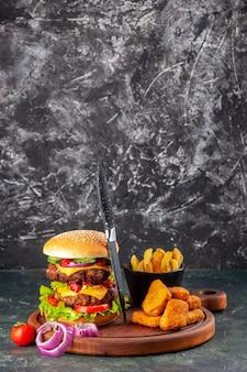 Smaczne domowe pomidory kanapki papryka na drewnianej desce do krojenia cebula pomidor z łodygą nuggets z kurczaka frytki na powierzchni ciemnego koloru