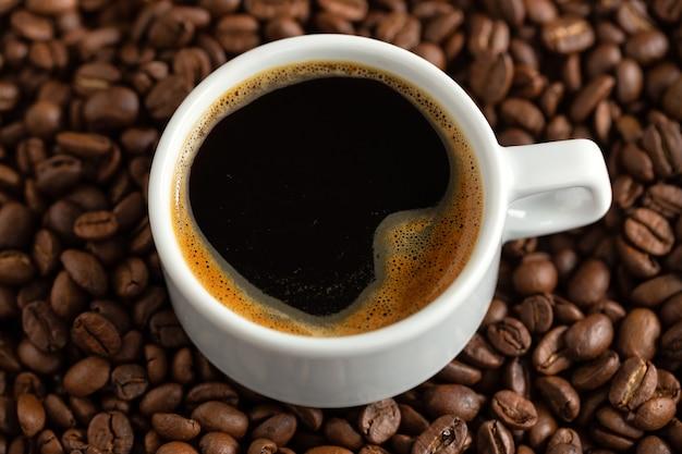 Smaczne espresso na parze w filiżance z ziaren kawy. zbliżenie