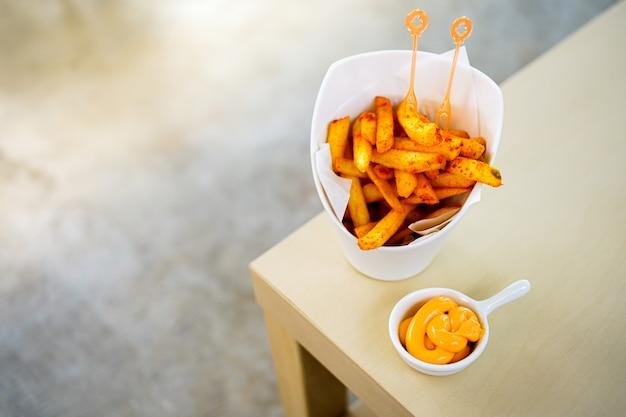 Smaczne frytki z dipem serowym na białym talerzu, na tle drewniany stół