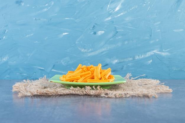 Smaczne frytki ziemniaczane na talerzu na fakturze na marmurowej powierzchni