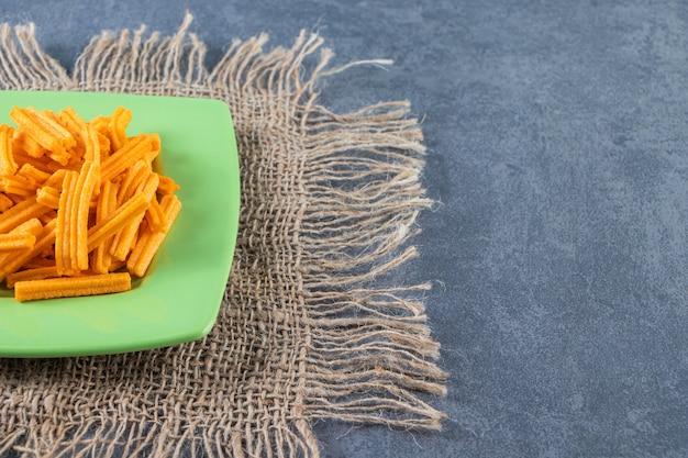 Smaczne frytki ziemniaczane na talerzu na fakturze, na marmurowym tle.