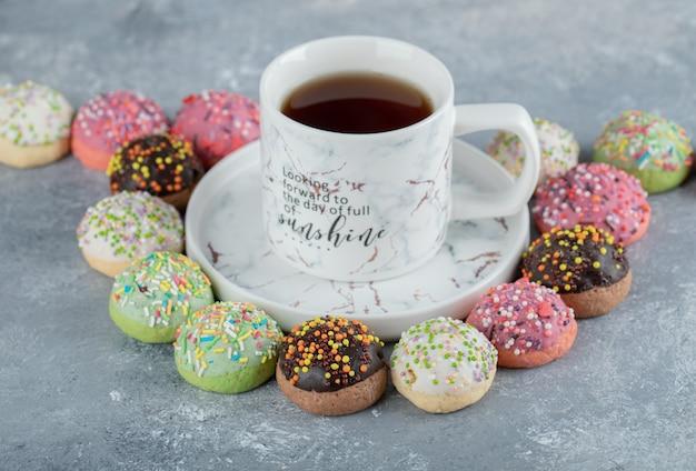 Smaczne glazurowane ciasteczka wokół filiżanki herbaty.