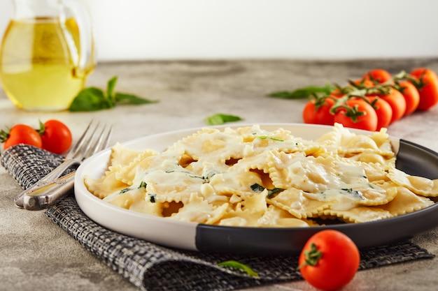Smaczne gotowane ravioli z sosem śmietanowym, pomidorami koktajlowymi, olejem słonecznikowym i bazylią na jasnej drewnianej powierzchni. skopiuj miejsce