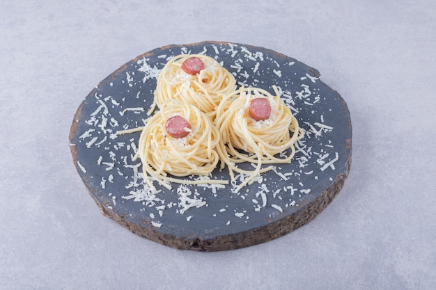 Smaczne gotowane spaghetti z kiełbaskami na kawałku drewna.