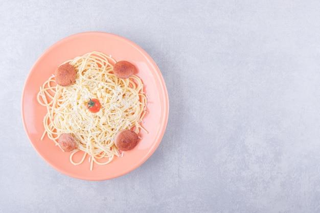 Smaczne gotowane spaghetti z kiełbaskami na pomarańczowym talerzu.