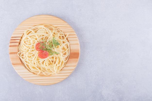 Smaczne gotowane spaghetti z pomidorami na drewnianym talerzu.