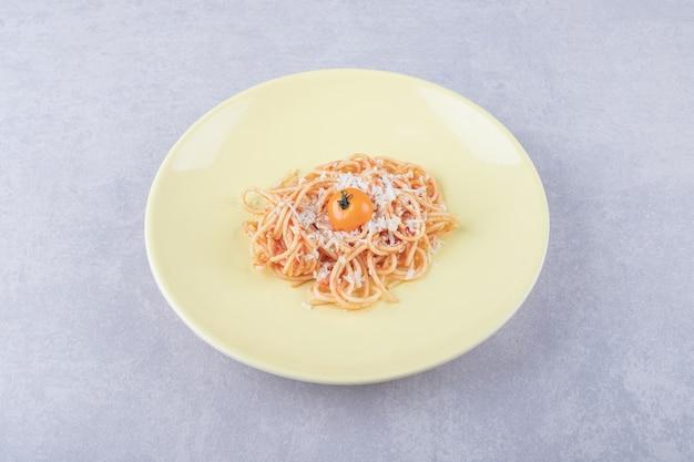 Smaczne gotowane spaghetti z pomidorami na żółtym talerzu.