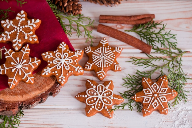 Smaczne i pachnące ciasteczka z kawałkami czekolady są kruszone cukrem pudrem z wielobarwnymi lampkami na stole. wesołych świąt