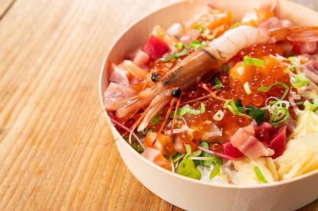 Smaczne i pyszne chirashi japońskie jedzenie na drewnianym stole, zdrowe odżywianie i dobrze jeść koncepcja. zabierz domowe jedzenie. ścieśniać