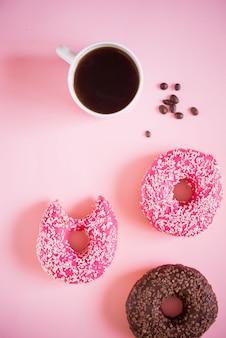 Smaczne i pyszne pączki z różowym lukrem i proszkiem z filiżanką aromatycznej kawy na białej powierzchni