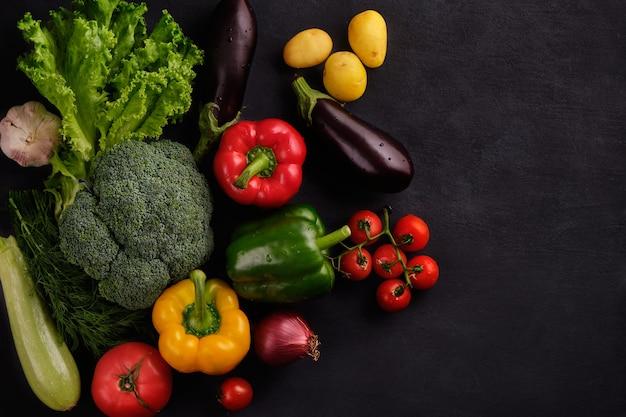 Smaczne i zdrowe jedzenie. świeże i soczyste wielobarwne warzywa na czarnym tle z bliska