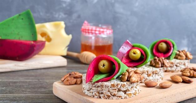 Smaczne i zdrowe kanapki z serem rzemieślniczym, oliwkami, orzechami i pieczywem pełnoziarnistym na desce. oryginalne przekąski na imprezę.