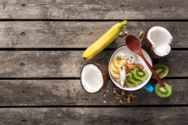 Smaczne i zdrowe śniadanie. miska owocowy jogurt kokosowy z muesli na drewnianym stole kopiowanie miejsca widok z góry zdrowe wegańskie jedzenie koncepcja