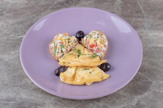 Smaczne jajka sadzone na fioletowym talerzu.