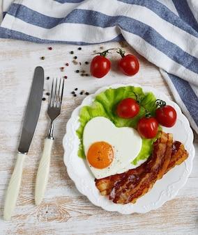 Smaczne jajko sadzone w kształcie serca podawane na białym talerzu z boczkiem sałatka pomidorowa liście papryki drewniane tle walentynki rano