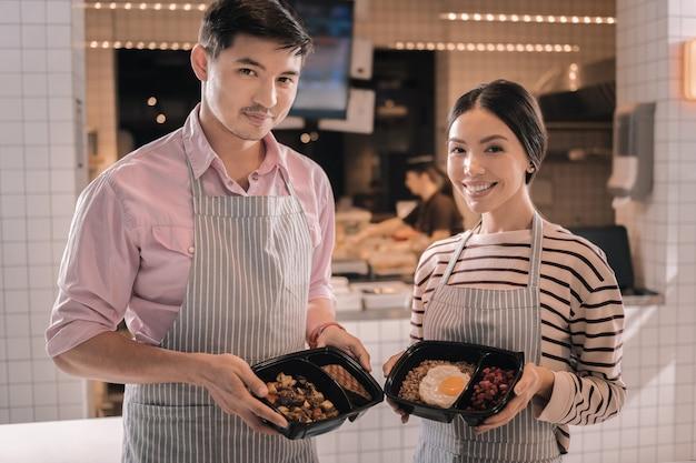 Smaczne jedzenie. dwóch sympatycznych, rozpromienionych kelnerów trzymających ładne pudełka na lunch ze smacznym jedzeniem, stojących w pobliżu kuchni