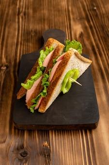 Smaczne kanapki na brązowym drewnianym biurku