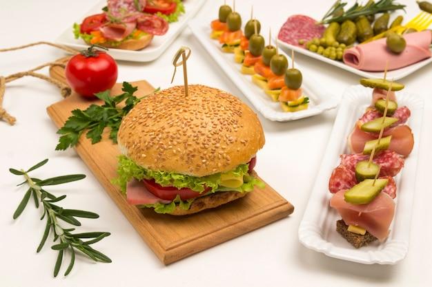 Smaczne kanapki z łososiem, boczkiem, serem, piklami na białym tle