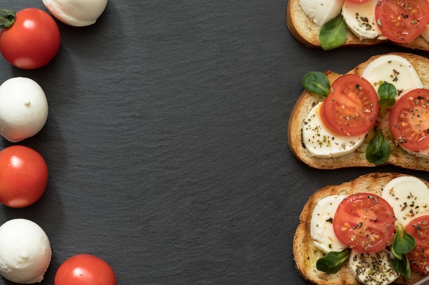 Smaczne kanapki z mozzarellą i pomidorami koktajlowymi na talerzu łupkowym, płaskie.